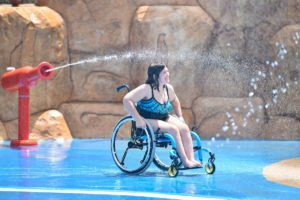 Girl in wheelchair playing on a splash pad